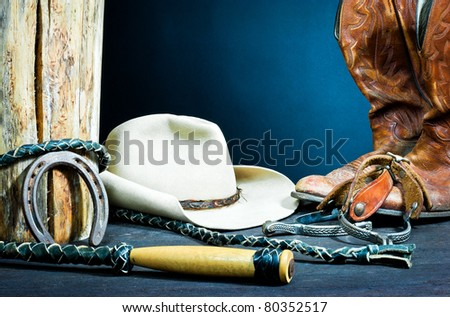 ,Cowboy boots,horseshoe,whip,spurs and hat on wood, - stock photo