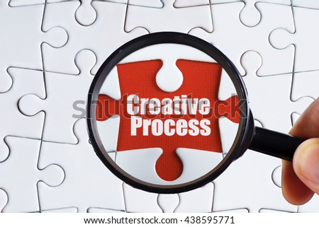 """""""Creative process"""" text on red missing jigsaw puzzle with man right hand hold black magnifying glass searching for missing puzzle peace - business and finance concept - stock photo"""