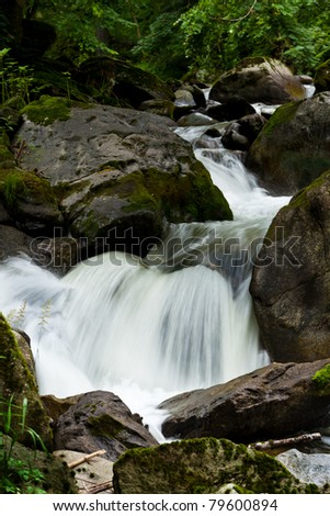 creek with water and stones in the mountains - stock photo