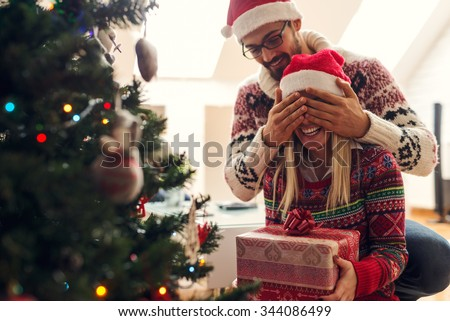 Cropped shot of a man surprising his girlfriend with a Christmas gift. - stock photo