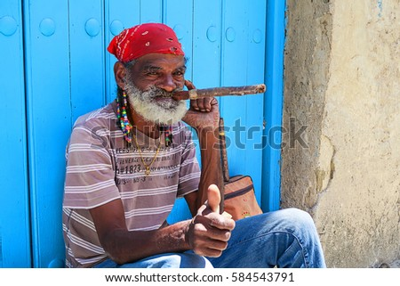Cuba, Havana - 07 April, 2016: a local star with cigar - man in red bandanna and dreadlocks posing for tourists in Havana, Cuba - the greatest producer of cigars