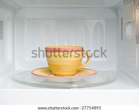 cup of coffee in microwave - stock photo
