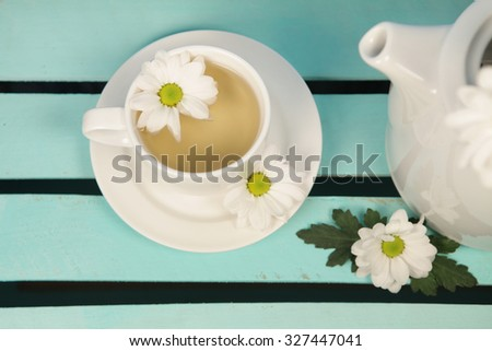 Cup of soothing chamomile tea on rustic wooden  background  - stock photo