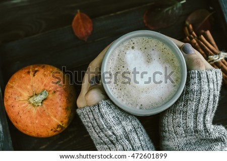 Cup of Spicy pumpkin latte in Woman's hands in gray sweater on the brown wooden table with red leaves. Cozy autumn mood