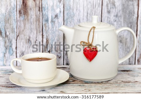 Cup of tea and teapot with heart shape on wooden table
