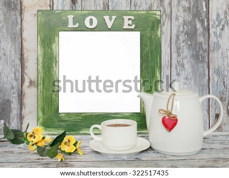 Cup of tea and teapot with heart shape on wooden table.  Summer Flowers,green frame with place  for text  - stock photo