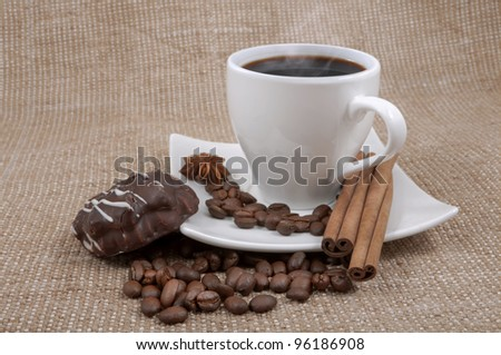 cup with coffee stands on a saucer with the spilled grain, chocolate thin captain, anise, by the sticks of cinnamon on a background fabric from sacking