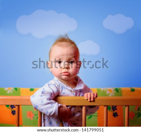 Cut baby girl in her crib - stock photo