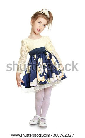 cute beautiful little blonde girl with the bow on her head in elegant satin long dress and white stockings. Girl looking out the top-Isolated on white background - stock photo
