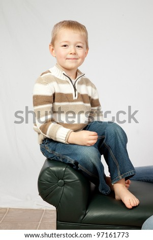 Cute blond boy sitting on the arm rest of a bench, and looking at the camera with a happy smile