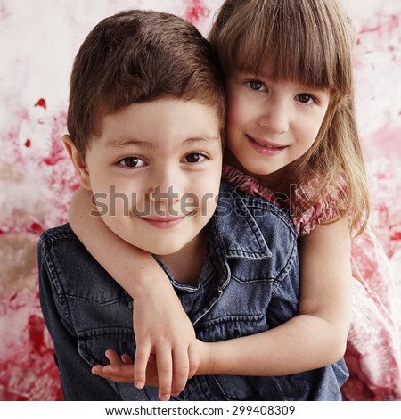cute brother and sister hugging each other - stock photo