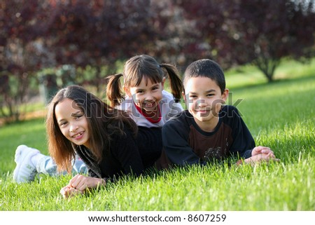 3 cute children of diverse nationalities outdoors - stock photo