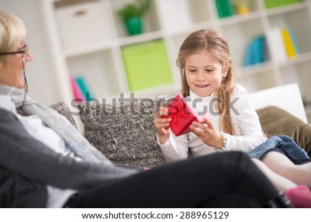 Cute girl opening gift presented by grandmother with surprise face - stock photo