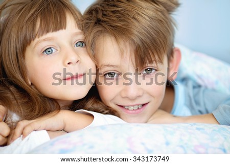 cute kids, brother with sister, waking up in bed at home - stock photo