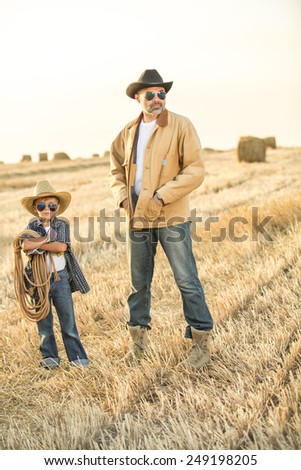 Cute little cowboy with his father, focus on boy, daylight - stock photo