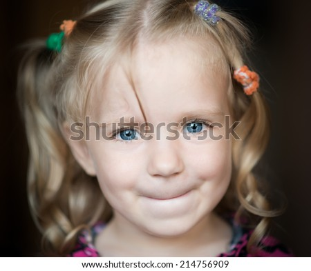Cute little girl smiling over dark background.
