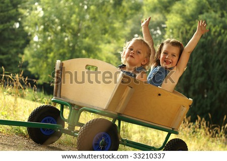 2 Cute little girls in a cart - stock photo