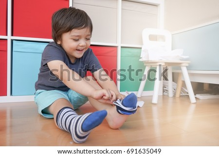 cute little kid sitting next to tablet and learning how to put the socks on by
