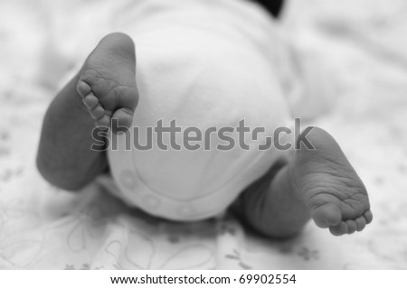cute little new born baby's feet. black-white image. new born baby is trying to crawl. - stock photo
