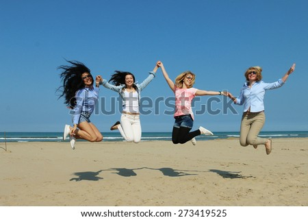 4 cute multiethnic girlfriends jumping in the air on the beach posing for a photo under blue sky and bright sunshine