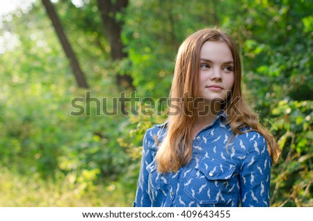 cute red hair girl teenager in a forrest at nature