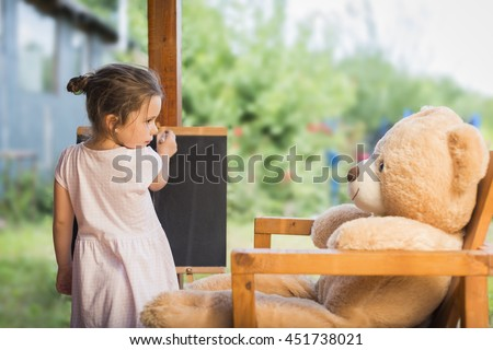 Cute toddler playing teacher role game outdoors. Little child drawing with pieces of chalk on a blackboard. Happy kid leaning letters and numbers. Children education concept - stock photo