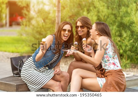3 cute women, ice cream parlors, while laughing  - stock photo