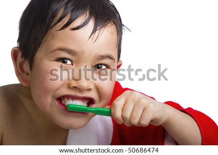 Cute young boy brushing his teeth fresh out of the shower isolated on white background