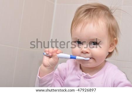 Cute young girl brushing her teeth. Studio shot - stock photo