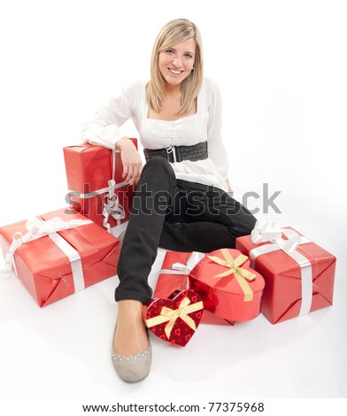 Cute young woman surrounded by packages, some of the heart shaped - stock photo