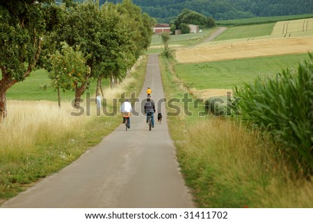 Cyclists and dog are walking on a road