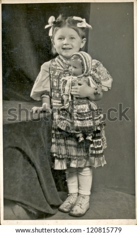 CZECHOSLOVAKIA, CIRCA 1950 - Girl posing in the national costume in a photographic studio (holding porcelain doll) - Circa 1950