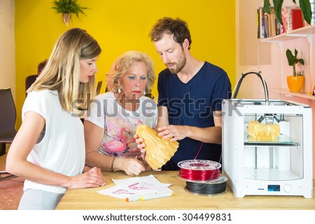 3D designers discussing and examining a product at counter in a 3D printing studio - stock photo
