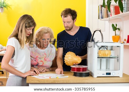 3D designers discussing while holding product at counter in printing studio - stock photo