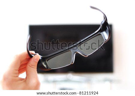 3D-glasses in the hand against TV-screen - stock photo