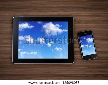 3d illustration of modern mobile devices on wooden table with cloudy sky on screen. Cloud computing concept. - stock photo