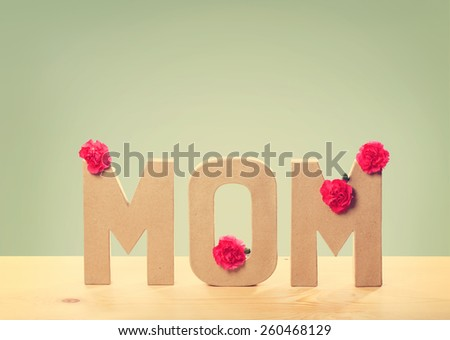 3D MOM Text with Fresh Carnation Flowers Standing on the Wooden Table with Light Green Background - stock photo