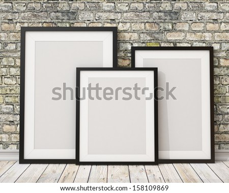 3d of three blank black picture frames on the old brick wall and the wooden floor, background - stock photo