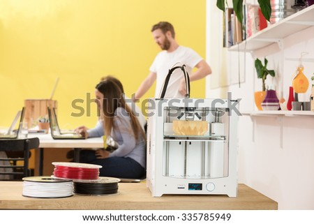 3D printer with products on counter with designers working in background at creative studio - stock photo