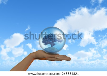 3D render of a female hand holding a tree in a globe against a blue sky background - stock photo