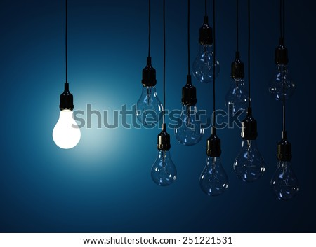 3d render  of hanging light bulbs with glowing one isolated on dark blue background - stock photo