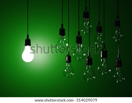 3d render of hanging light bulbs with glowing one isolated on dark green background - stock photo