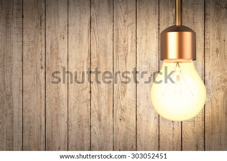 3d rendered hanging light bulb with timber wall background - stock photo