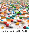 3D rendered illustration of countless pills and capsules scattered over a white, reflective surface - stock photo