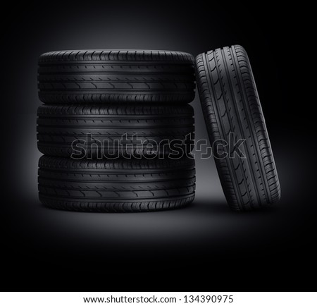 3d rendering of a 4 car tires on a black background - stock photo