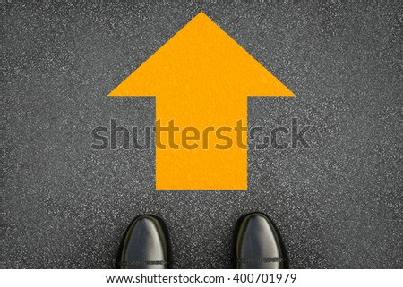 3d rendering yellow arrow sign with black leather shoes on street  - stock photo