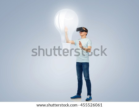 3d technology, virtual reality, entertainment, cyberspace and people concept - happy young man with virtual reality headset or 3d glasses playing game and touching light bulb projection