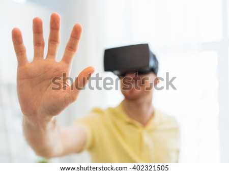 3d technology, virtual reality, gaming, entertainment and people concept - close up of happy young man with virtual reality headset or 3d glasses playing videogame at home - stock photo