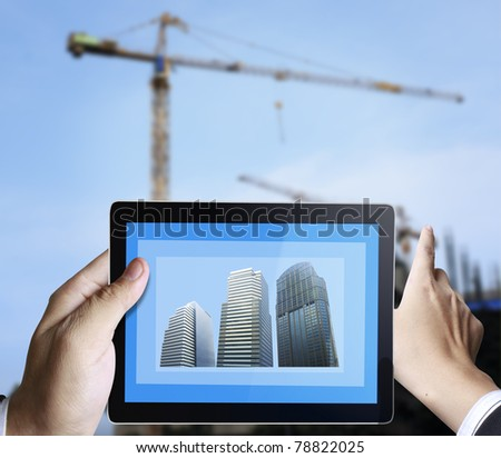 3d touchpad ,hand holding a touchpad pc with the construction of buildings - stock photo