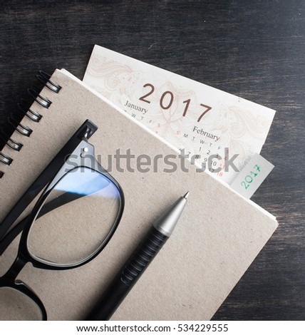 Daily note book with New Year 2017 office organizer calendar on wood table